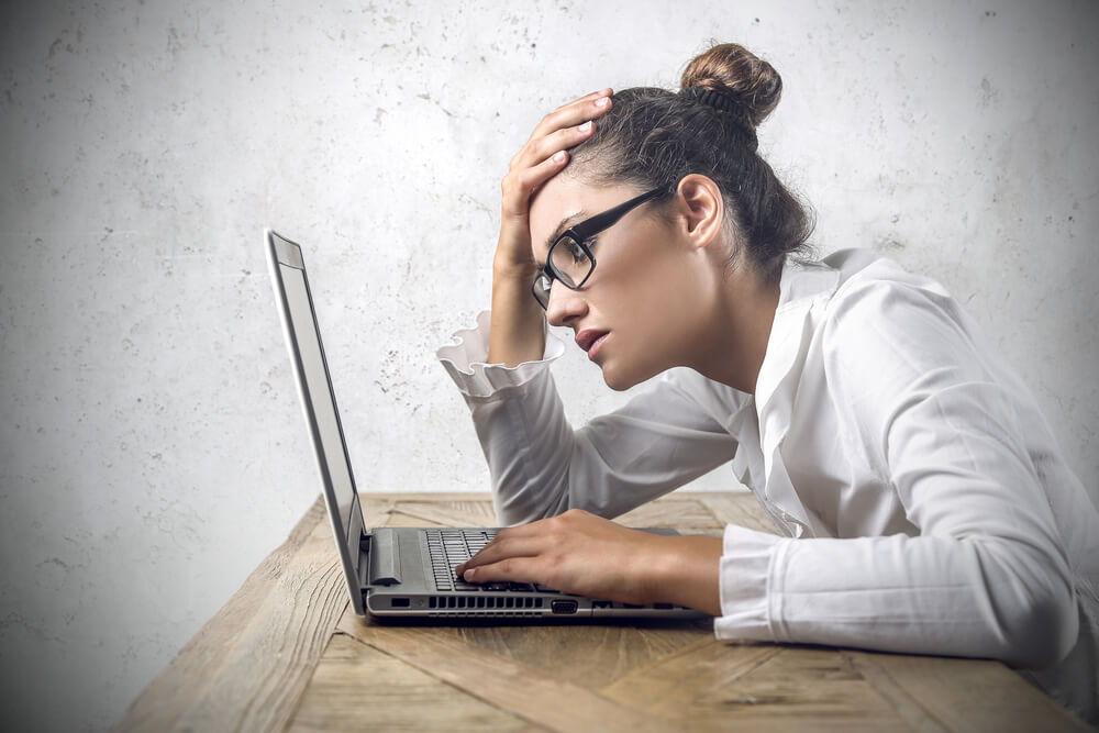 exasperated woman at desk with laptop